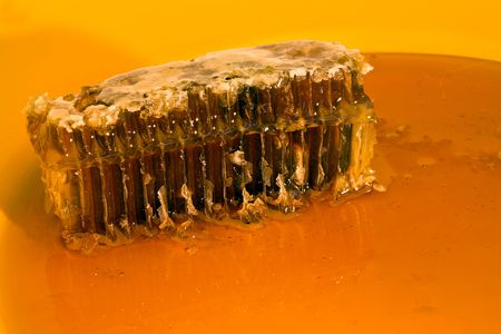 Natural Honey and Honeycomb on Yellow Ceramic Plate; Close-up