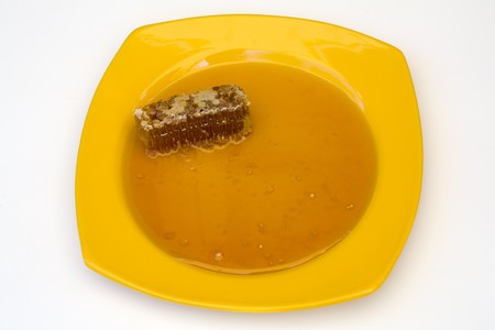 Closeup of Natural Honey and Honeycomb on Yellow Plate Imagens