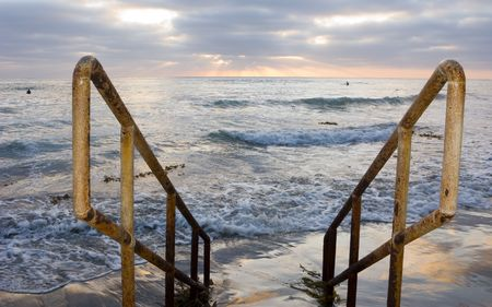 handrails: Rusty Yellow Handrails and Sunset Surfers in Ocean Waves