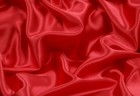 Folded red satin textile background; close up photo