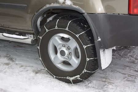tire tread: Affixed Metal Snow Chain to Vehicle Tire Stock Photo