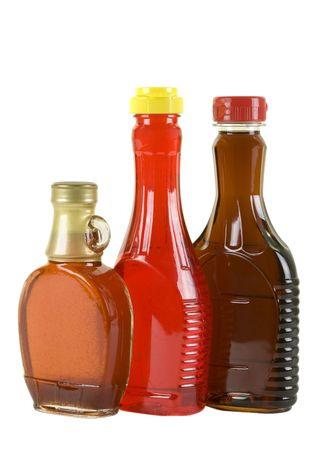 Three bottles with strawberry and maple syrup, isolated Stock Photo