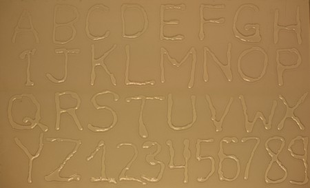 Water letters and numbers on tanned glass surface Фото со стока
