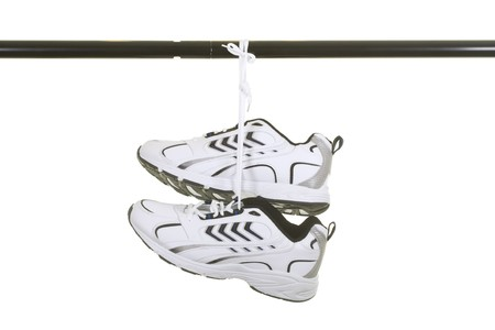 hang up: New sneakers hanged on painted metal bar; isolated on white background