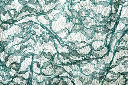 Green wrinkled lace on white spandex background, macro view