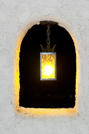 Outdoor night lamp in stucco wall arch window Banco de Imagens