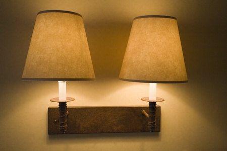 Two wall lamps in ON position in dark room