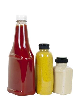 salsa de tomate: Salsa de tomate, mostaza picante de color marrón y crema de rábano picante en botellas, ángulo de visión, sobre fondo blanco