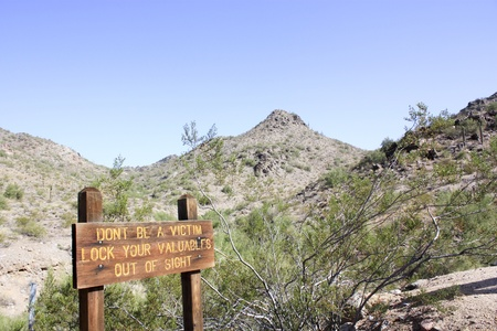 A rustic wood warning sign in the park of Phoenix, AZ photo
