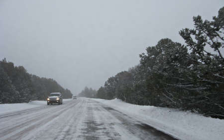 Cars moving carefully in blizzard on snowy road Stock Photo