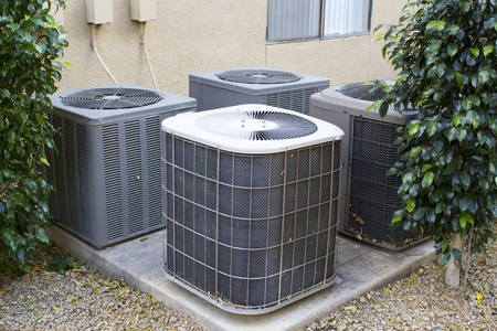 refrigerant: Residential air conditioner compressor units near building