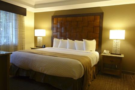 nightstands: Interior of modern luxury hotel bedroom with nightstands and lamps