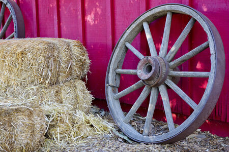 ranch house: Wooden wheel and stack of hay in next to red ranch house wall Stock Photo
