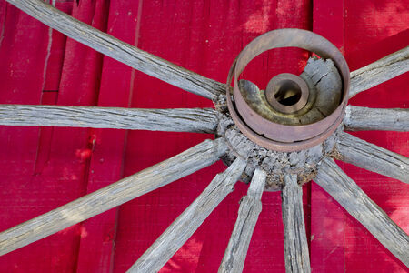 hubcap: Wooden spokes and hub with rusty iron rings of old cart wheel on red wall background