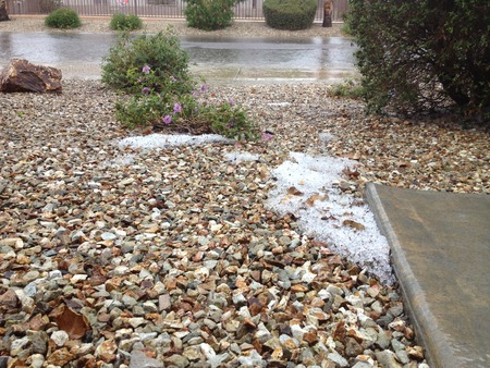 az: Spring storm floods streets and drops patches of snow in front yards of desert city, Phoenix, AZ