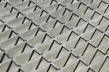 metal grate: Protective metal grate with rods and plates over water drainage manhole Stock Photo