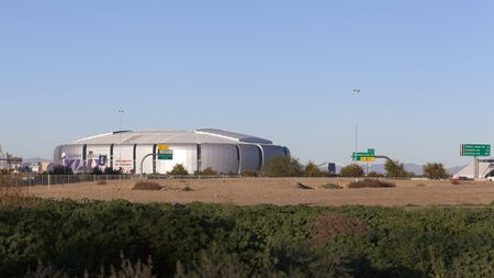 undeveloped: GLENDALE, AZ - JANUARY 24, 2015: Undeveloped city area lot contrasting University of Phoenix Cardinal Stadium that hosts Super Bowl XLIX in Glendale, Phoenix metro, Arizona. New England Patriots play Seattle Seahawks on February 1, 2015