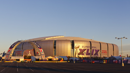 cast in place: GLENDALE, AZ - JANUARY 24, 2015: Gold evening color cast on silver dome of University of Phoenix Arizona Cardinal Stadium that dressed up for Super Bowl XLIX taking place on  February 1, 2015