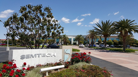headquarter: CAMARILLO, CA - APRIL 8, 2015: Semtech front sign and logo with red roses in foreground and magnolia tree, palms and main road to the corporate headquarter office in Camarillo, California