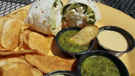 tortilla wrap: Flour tortilla wrap stuffed with rice and vegetables served with potato chips and salsa Stock Photo
