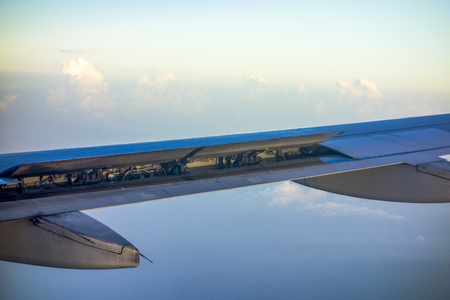 wingtips: Ailerons and wing flaps at work during aircraft maneuver Stock Photo