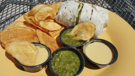 tortilla wrap: Lunch with wheat flour tortilla wrap, potato chips and green salsa