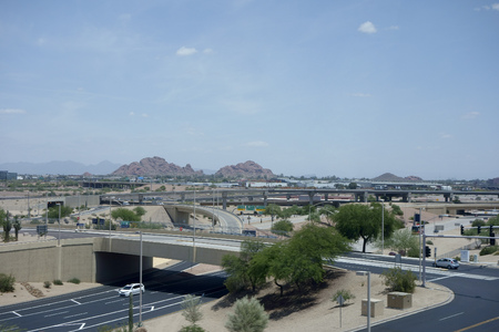 az: PHOENIX, AZ - MAY 23, 2015: Mid-day rare low traffic in and out of Phoenix Sky Harbor International Airport near East Economy Parking Lot with Papago Park buttes in the distance, Arizona