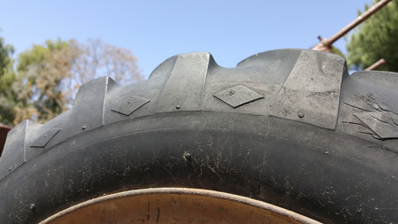 lugs: Black Off-the-road tire sidewall with oversized tread lugs along its shoulder