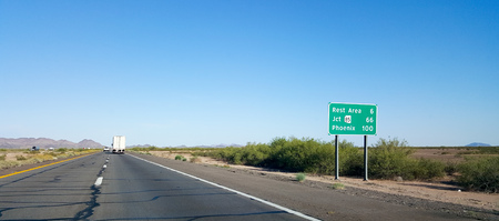 eastward: Road sign in the desert on Eastbound Interstate-10 showing 100 mile distance to the capital city of Phoenix, Arizona.