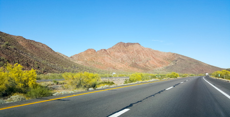 eastward: Buttes, hills and low rise mountains along Interstate-10 east of city of Quartzsite.in Arizona desert covered with drought and extreme heat resistant vegetation.