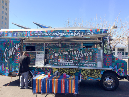paintjob: PHOENIX, AZ - FEBRUARY 5, 2016: Emerson Fry Bread food truck with colorful paint job servicing a customer in designated lunch area of Phoenix downtown, Arizona