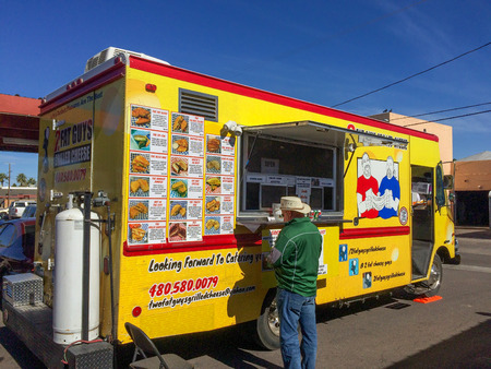 merchant: PHOENIX, AZ - FEBRUARY 5, 2016: A man buying lunch from Two Fat Guys Grilled Cheese food truck at designated outdoor spot in downtown of Phoenix, AZ Editorial