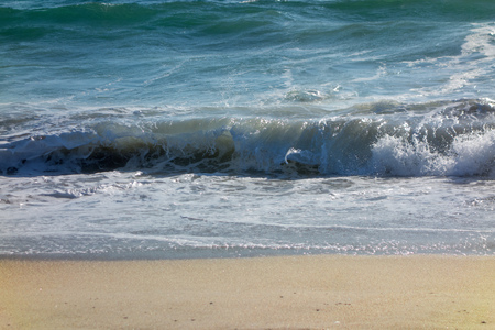 flattened: Wet yellow sand flattened by powerful rolling ocean waves