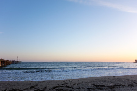 breezy: Breezy evening surf at Ventura city beach near historic wooden pear with a distant chain of Channel Islands, California