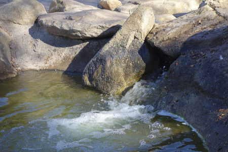 az: Green water flowing from decorative boulders and rocks, Cortez lake, small recreational park in North West Phoenix, AZ
