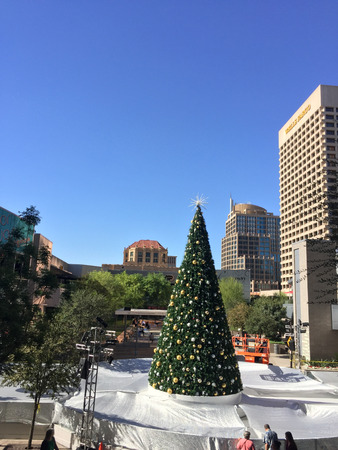 goldish: PHOENIX, AZ - NOVEMBER 17, 2016: White Christmas spirit created by protective highly reflective silver-white tarp covering downtown skating ring with decorated Christmas tree in sunny Phoenix, Arizona Editorial