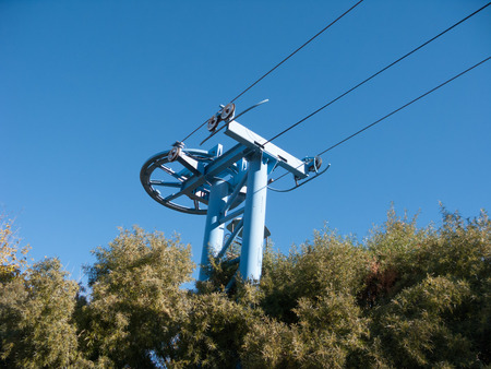 Towering support pilon, turning wheels and steel carrying cables of Sky Ride system