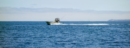 Fast moving fishing boat near Channel Islands west of Ventura coast, Southern California Stock Photo