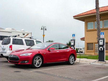 VENTURA, CA - JULY 4, 2013: Tesla electric car topping up its battery at a quick charging station while parked in Ventura Harbor Village