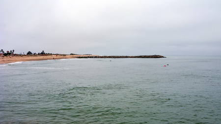 Morning gloomy weather over Pacific cost of Ventura county widely ignored by beach lovers seeking recreation near water edge, City of San Buenaventura, California