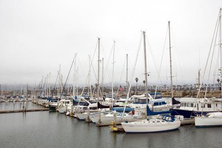 VENTURA, CA - JULY 4, 2013: Rows of white yachts anchored in Ventura harbor marina under overcast sky