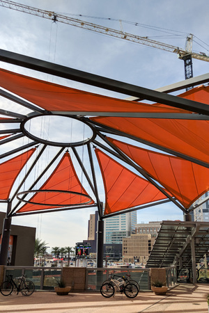 PHOENIX, AZ - FEBRUARY 2, 2018: Cozy recreation spot shaded by a colorful awning next to construction site with tower crane in background, downtown of Arizona capital city