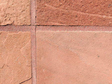 Closeup of weathered mineral sandstone tiles connected with cement grout