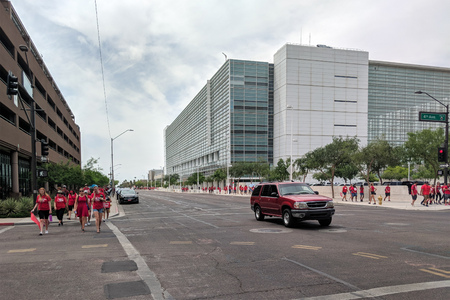 PHOENIX, AZ, USA - APRIL 26, 2018: Arizona teachers dressed up in red shirts marching back from first day of Walk-Out in Phoenix downtown along Jefferson Road, AZ