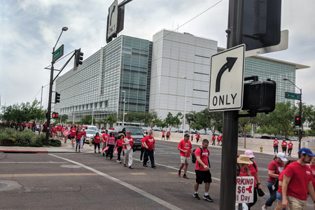 PHOENIX, AZ, USA - APRIL 26, 2018: Arizona teachers dressed up in red shirts marching back from first day of Walk-Out known as RedForEd in Phoenix downtown along Jefferson Road, AZ Publikacyjne