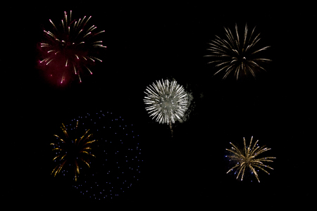 Sparkling round fireball charges exploding in pitch black sky of 4th of July celebration night Zdjęcie Seryjne