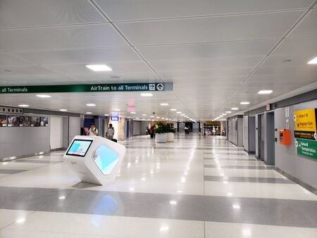 NEW YORK, NY, USA - SEPTEMBER 6, 2018: Pedestrian tunnel with signs to directing to Airtrain and all airport terminals in JFK, John F. Kennedy International Airport. Publikacyjne