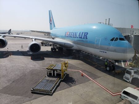 NEW YORK, NY, USA - SEPTEMBER 6, 2018: Airbus A380 of Korean Air parked at Terminal 1 in John F. Kennedy International Airport;  New Your cityscape in distant background Publikacyjne