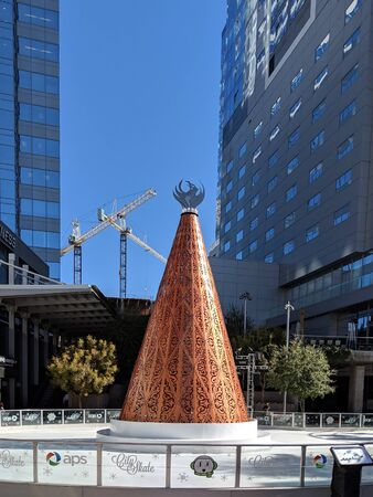 PHOENIX, AZ - NOVEMBER 26, 2018: City Skate with ornamental copper styled Christmas tree in the center of skate rink in always sunny Phoenix, Arizona