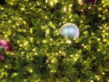 Holiday decorated green spruce twigs with shiny baubles and electric lights